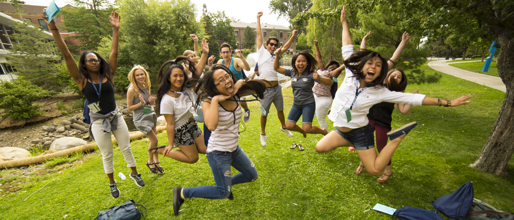 Orientation participants jump in unison on the grass.