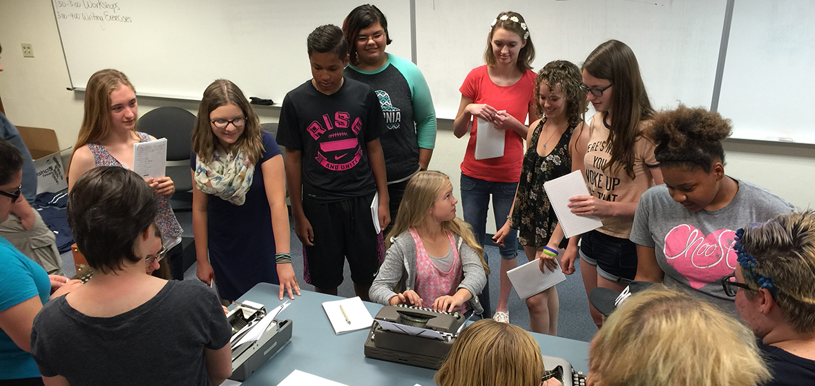 Students gathered around a table with typewriters