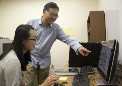 Faculty members Qi An and Xiaokun Yang shown working on a computer-based project.