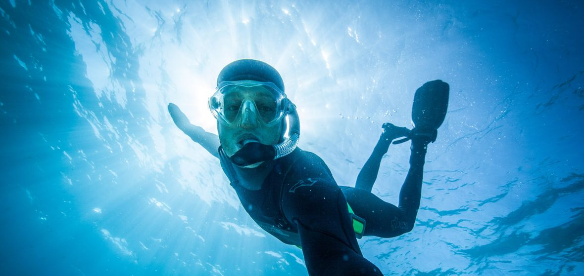 Photographer in wet suit takes photos under water in Lake Tahoe
