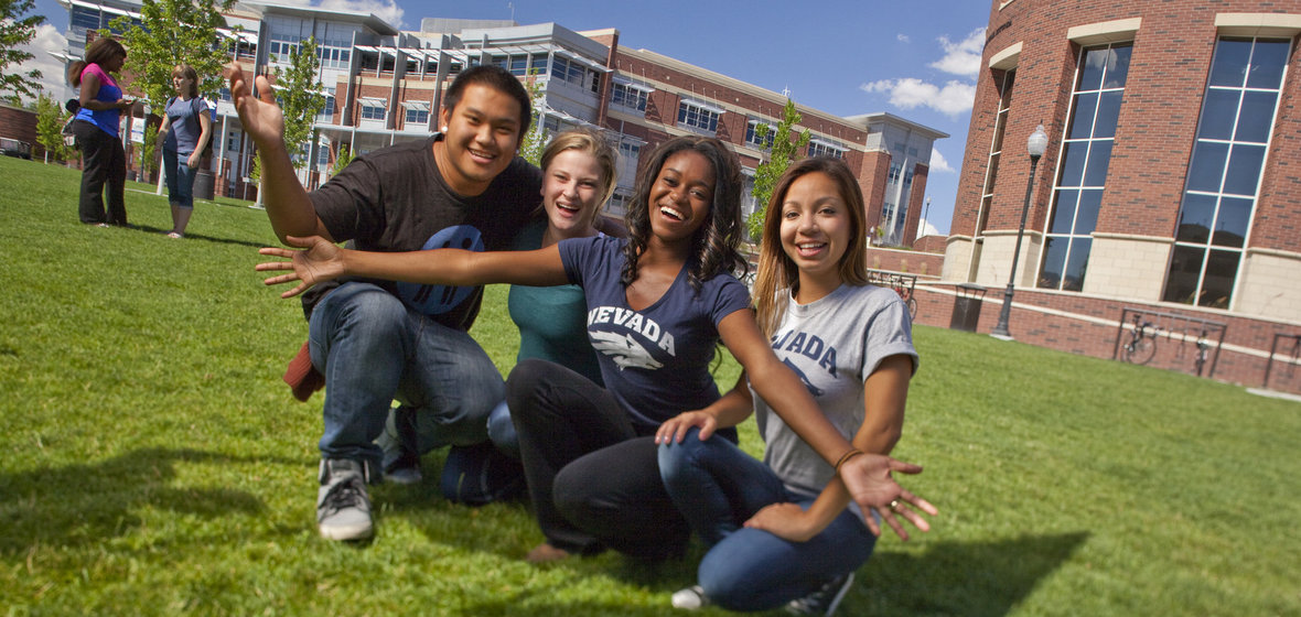 Four students in welcoming poses on the lawn in front of the Knowledge Center with the Student Union in the background
