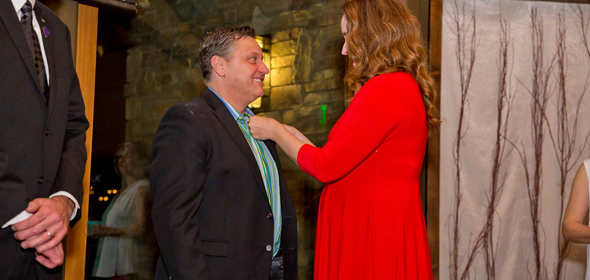 Anne McMillin, APR, pinning one of the newest APR designated professionals Todd Felts, APR.