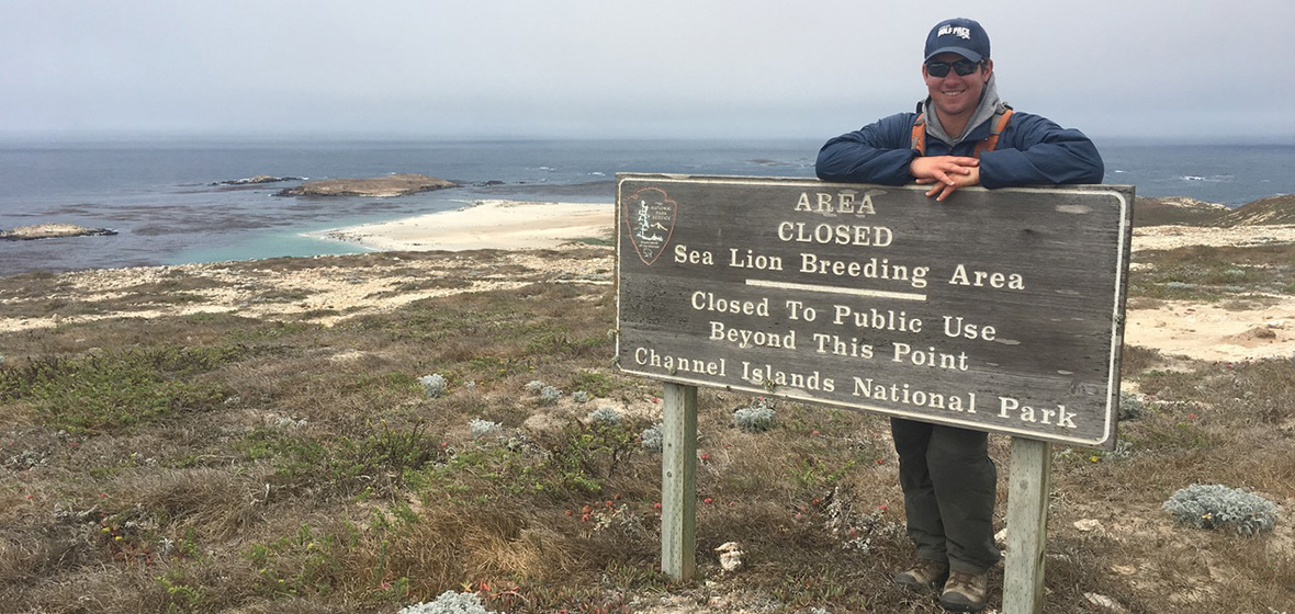 Chris Jazwa standing behind Channel Islands State Park sign with ocean in background