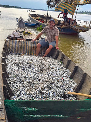 Zeb Hogan sits with a boatload of fish in a fishing boat on the Mekong river with other boats around him