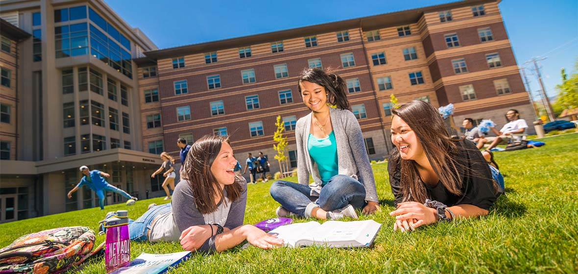 Three students lay or sit on the lawn in front of Peavine Hall on the University of Nevada, Reno campus