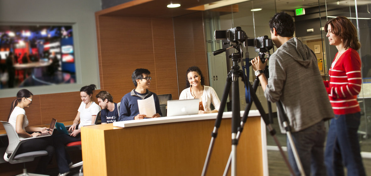 Students filming other students at a news desk