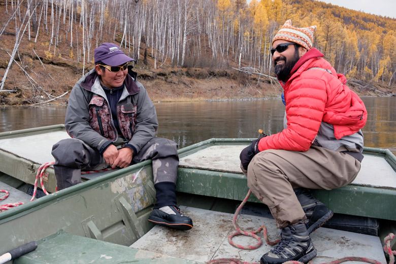 Sudeep Chandra sits on a boat with Mongolian fishing guide, Gonzarig.