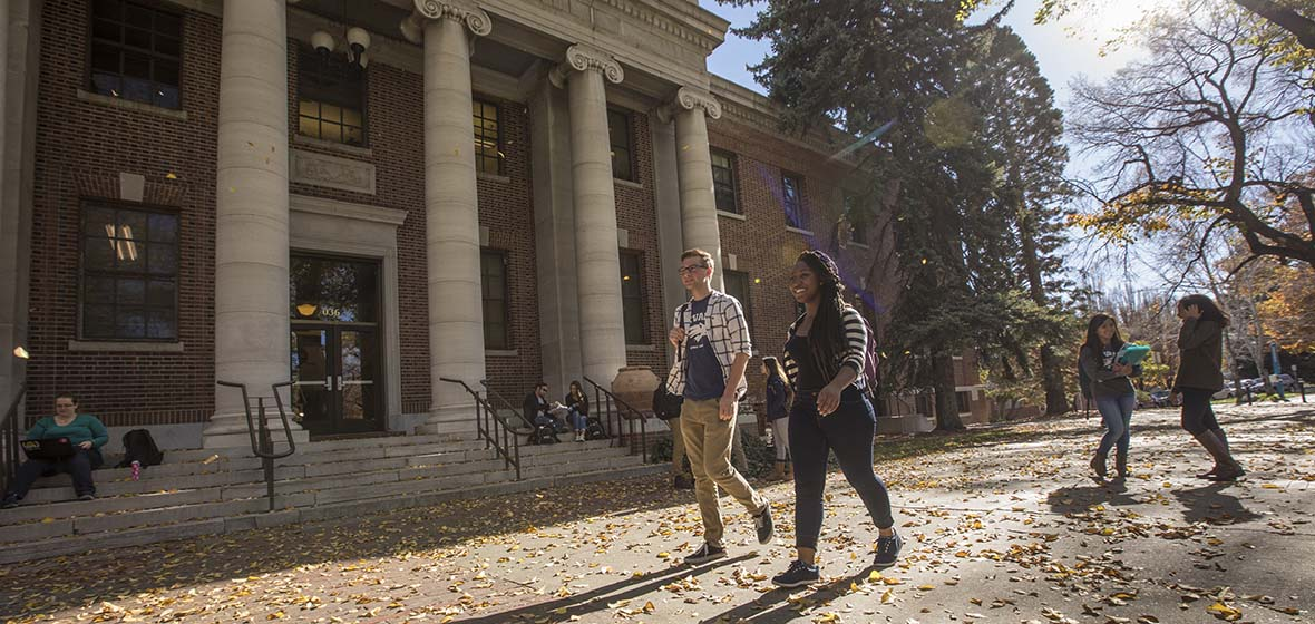 Students walking outside Mackay Science in the fall leaves