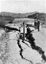Three people observe the damage caused by the 1915 Pleasent Valley Earthquake.