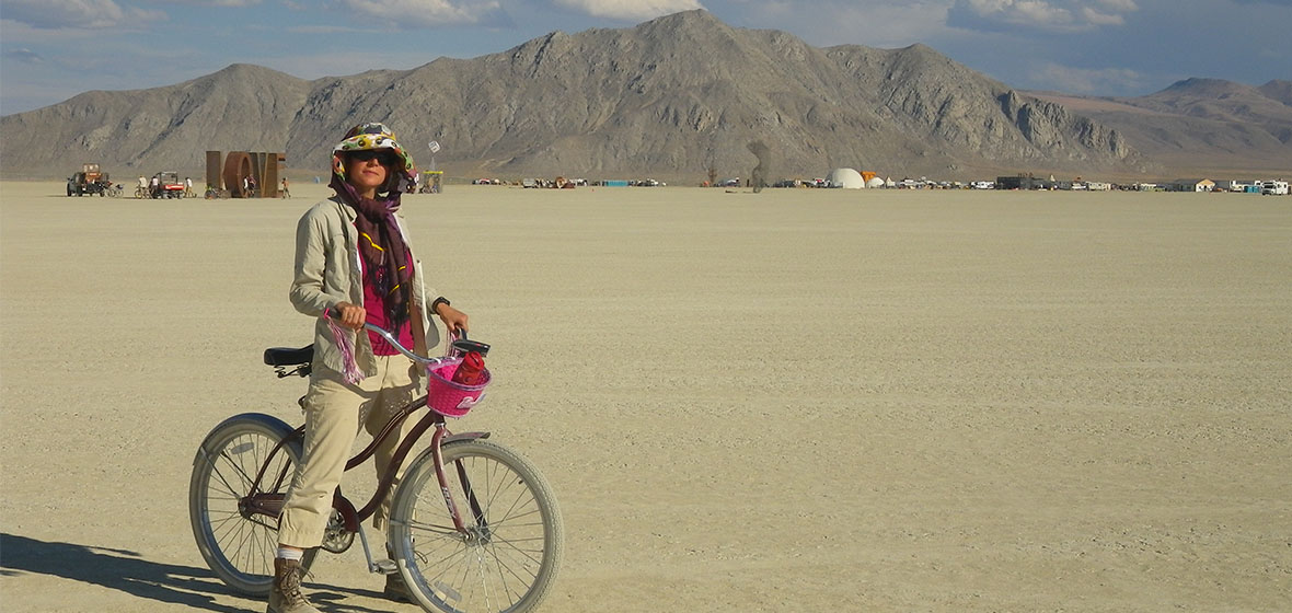 Professor Carolyn White poses for a photo with her bike on the Playa at Burning Man