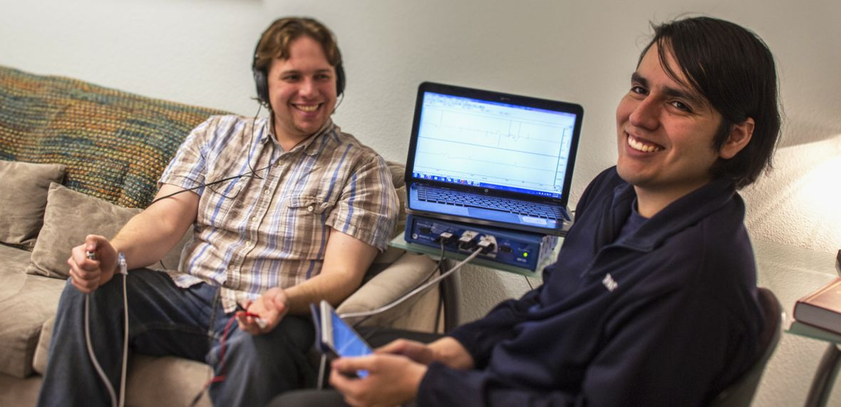A graduate student conducts social-psychology research with a human subject using a computer-based sensor