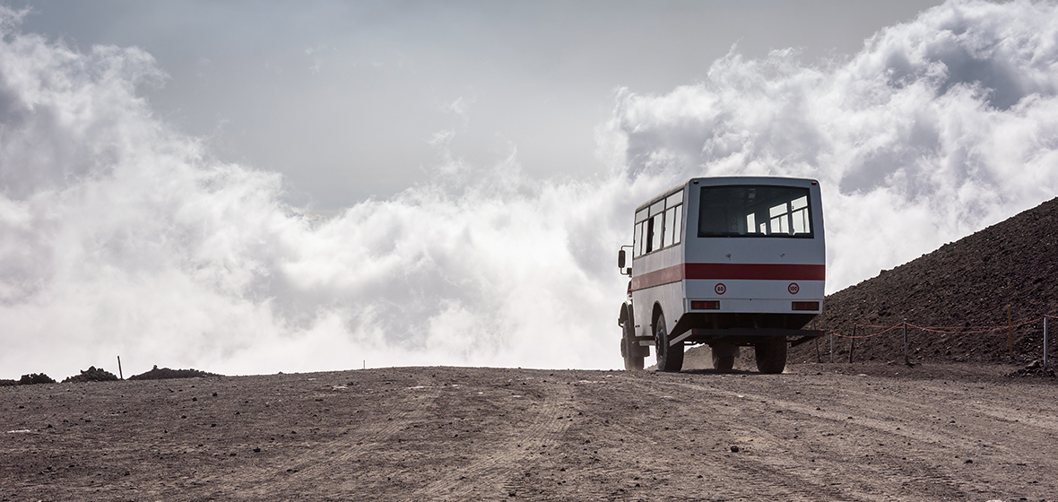 bus driving away on dirt road