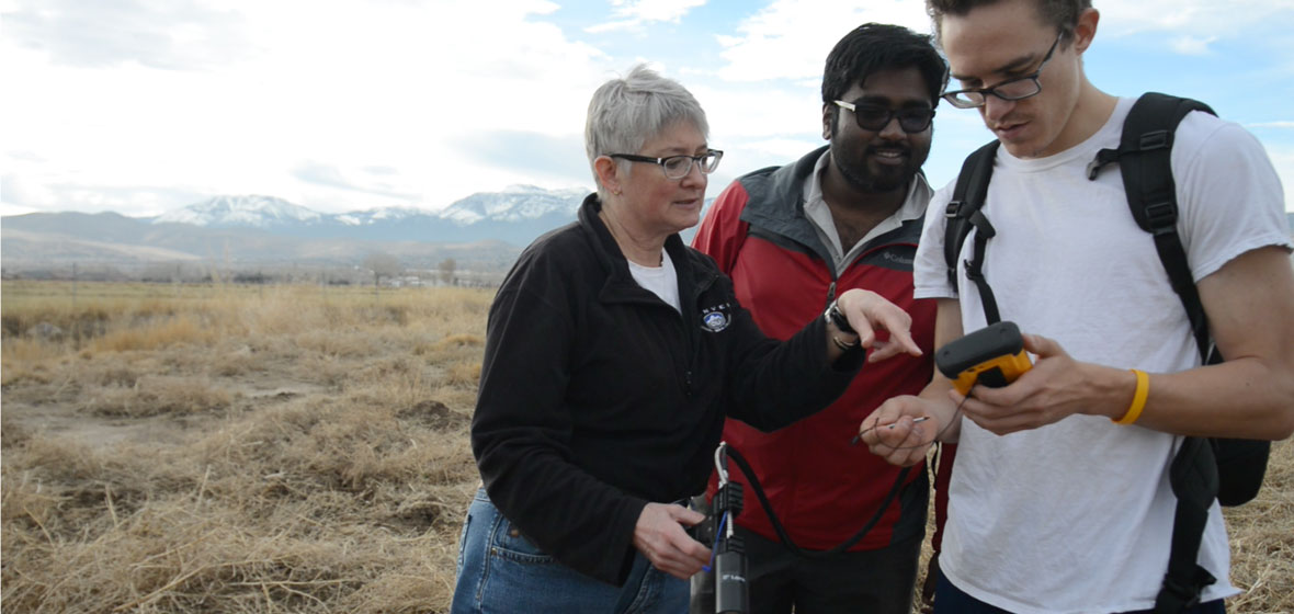 Professor Wendy Calvin with two students using a portable field spectrometer.