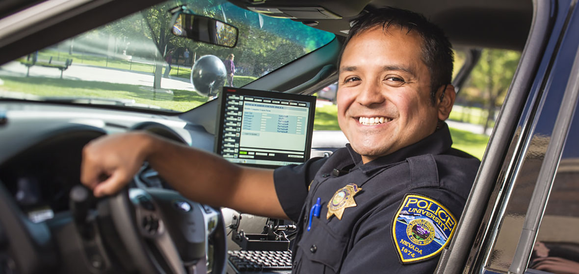 University police smiles from inside his police car.