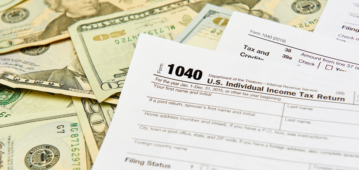 1040 income tax forms and twenty dollar bills