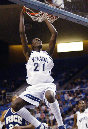 Nevada men's basketball player Kevinn Pinkney dunking the ball during a game against Rice University
