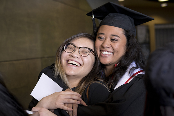 Graduates laughing and hugging at the Asian American & Pacific Islander Graduate Celebration