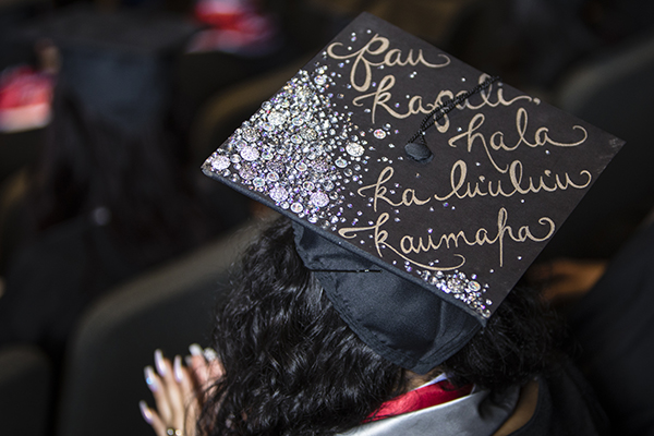 "A graduate's cap reads ""Pau kapali hala ka lu'ulu'u kaumaha"" at the Asian American & Pacific Islander Graduate Celebration"