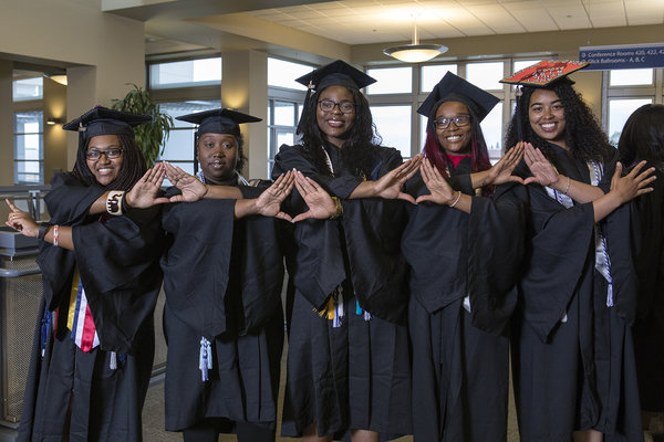 Graduates joining hands at the African Diaspora Graduate Celebration