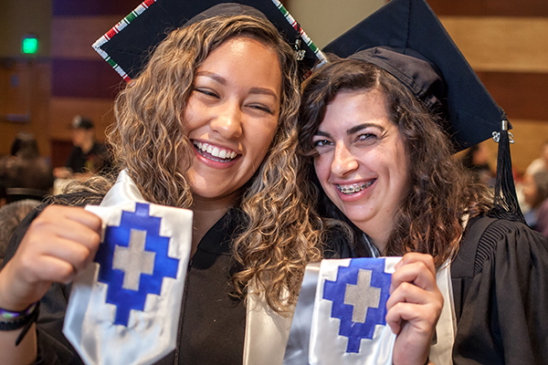 Two happy graduates at the American Indian & Alaskan Native Graduate Celebration