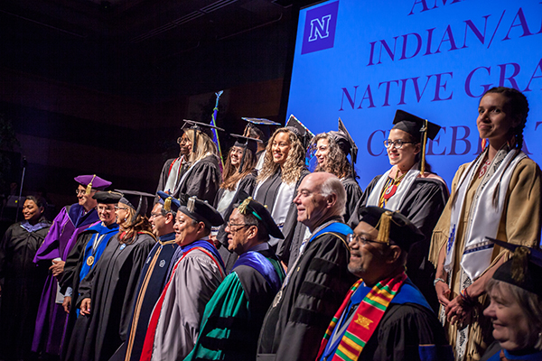 Graduates and faculty on stage at the American Indian & Alaskan Native Graduate Celebration
