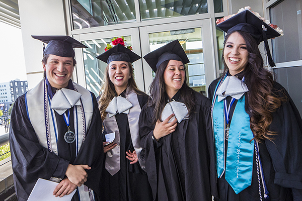 Four graduates outside the Latinx Graduate Celebration