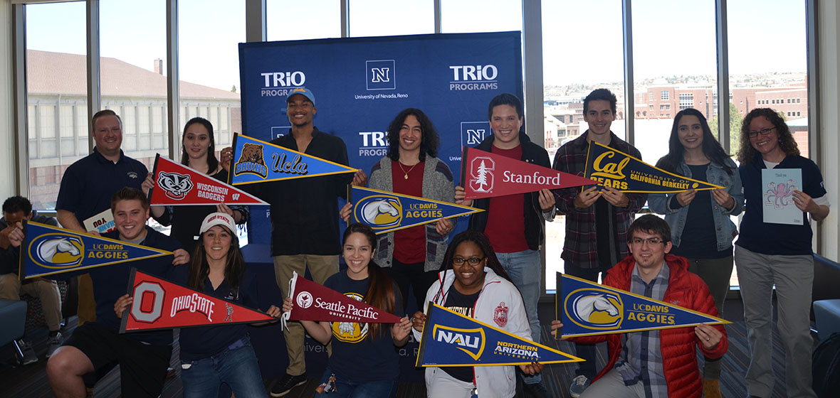 11 McNair Scholars holding their pennants from their chosen graduate schools with Perrry Fittrer on the far left.