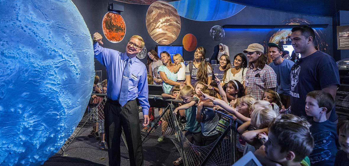 Dan Ruby points to a model of a planet among a group of young students visiting the Fleischmann Planetarium