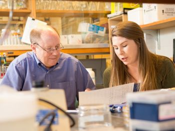 Professor discusses a paper report with a student in a biochemistry lab.