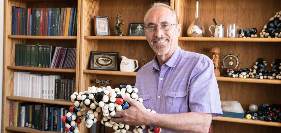 Professor holds a large-scale model of a molecule.