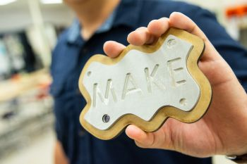 "A plaque made on the lasercutter in the makerspace; it has the word ""make"" on it."