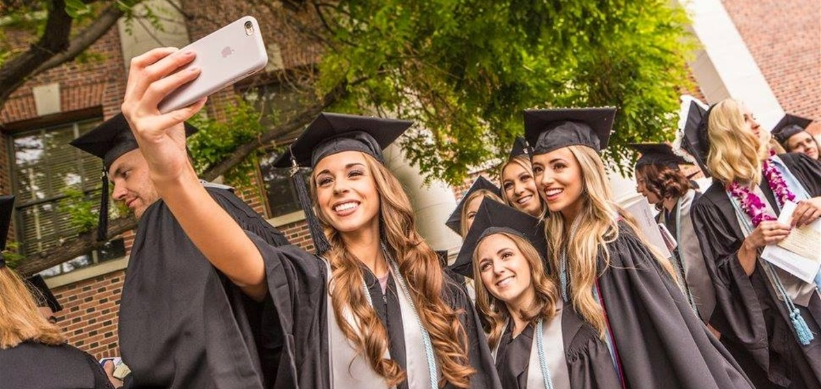Graduates taking selfies at commencement