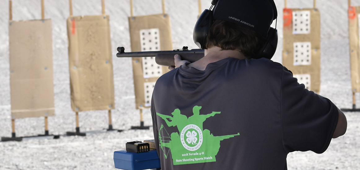 a boy with a 4-H shooting sports shirt shoots a rifle at a target