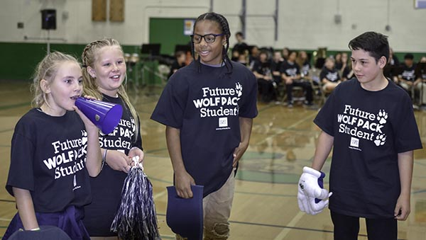 "Four middle school students at Clayton Middle School wear ""Future Wolf Pack Student"" T-shirts while leading fellow students in a cheer"