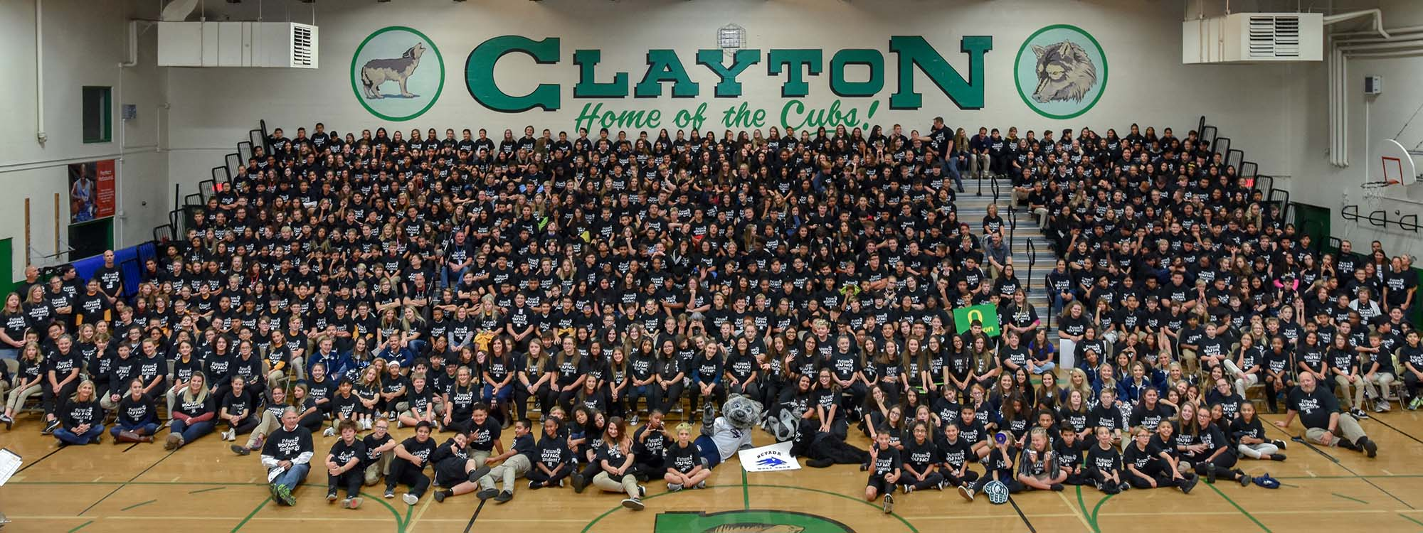 Clayton Middle School students pose for an all-school photo in new, black T-shirts at a College Day pep rally