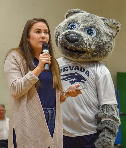 Student Body President Hannah Jackson address middle school students at a pep rally at Clayton Middle School with mascot Wolfie Jr. standing next to her