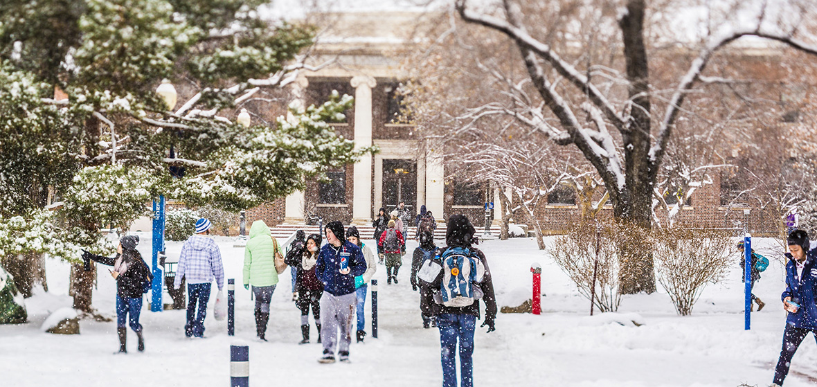 Students walking on campus in the snow.