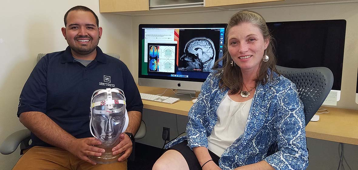 Hector Arciniega and Marian Berryhill are seated as a computer work station; Hector holds a clear 3-D representation of a human head.