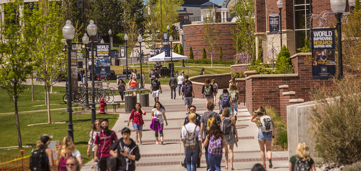 Image of students walking on campus in front of the Mathewson-IGT Knowledge Center looking north.