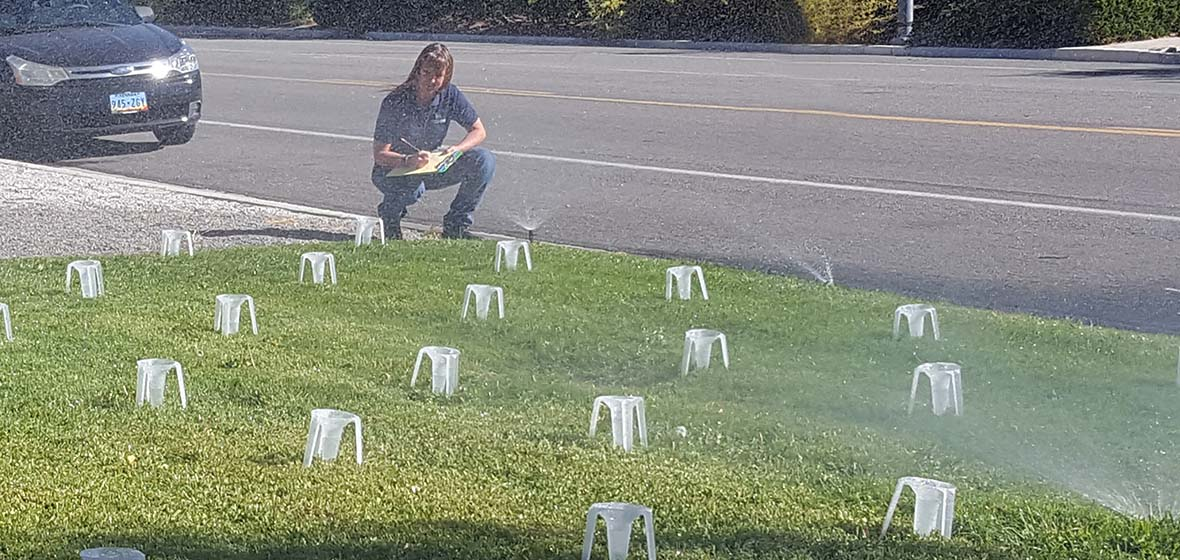 special plastic cups in grass catch water from sprinkers while kneeling woman takes measurements""