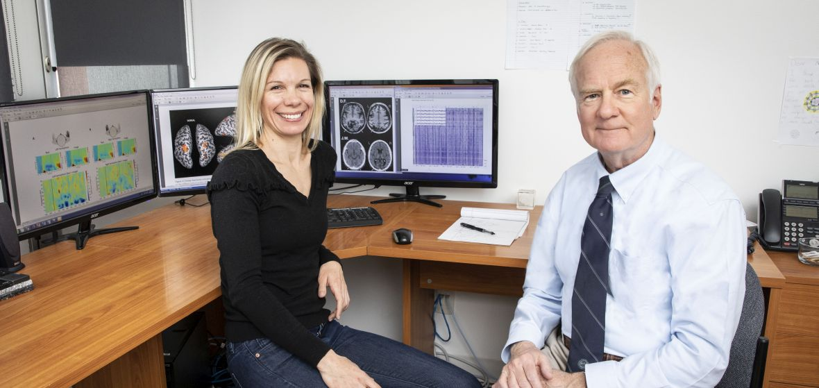 2 faculty member sitting at desk in office with neuroscience-related images on the computer screens