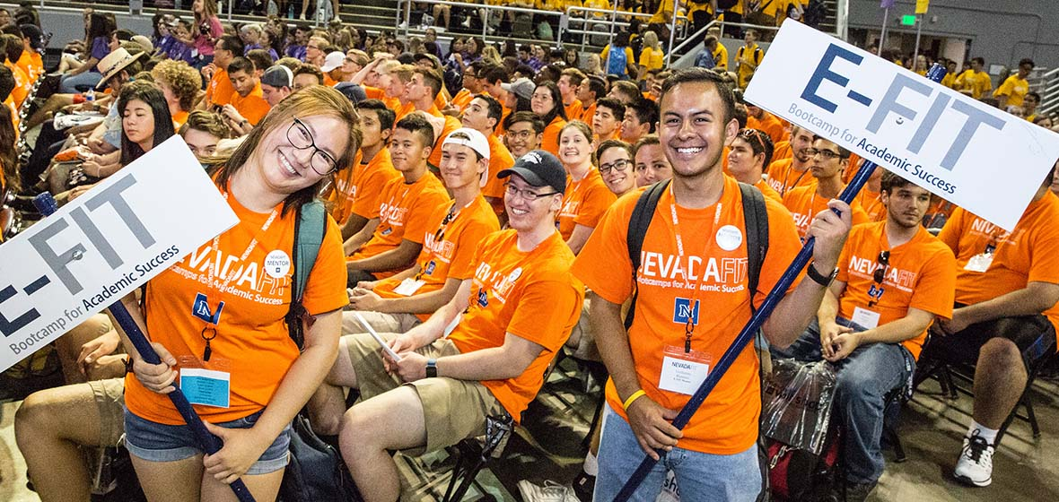 Students in orange shirts, some sitting and two standing, holding E-FIT signs as part of NevadaFIT's academic bootcamp kick-off ceremony in Lawlor Events Center.