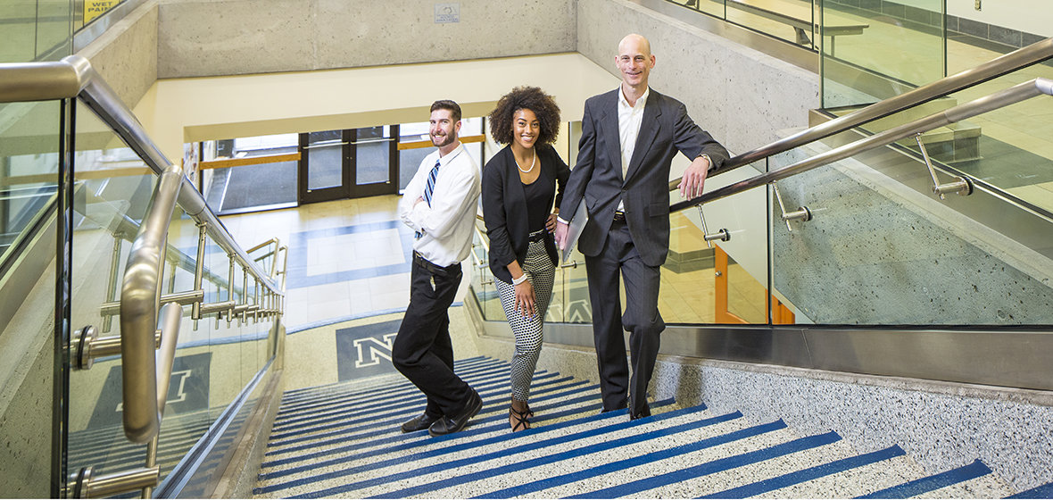 Three College of Business students on the stairs in the Ansari Business Building.