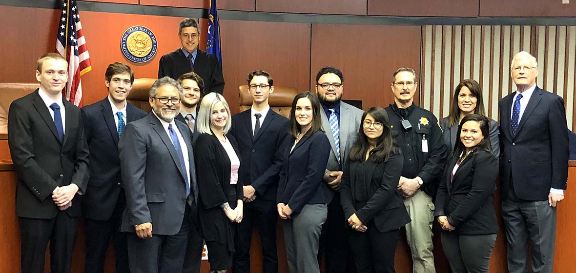 Mock trial group poses in courtroom