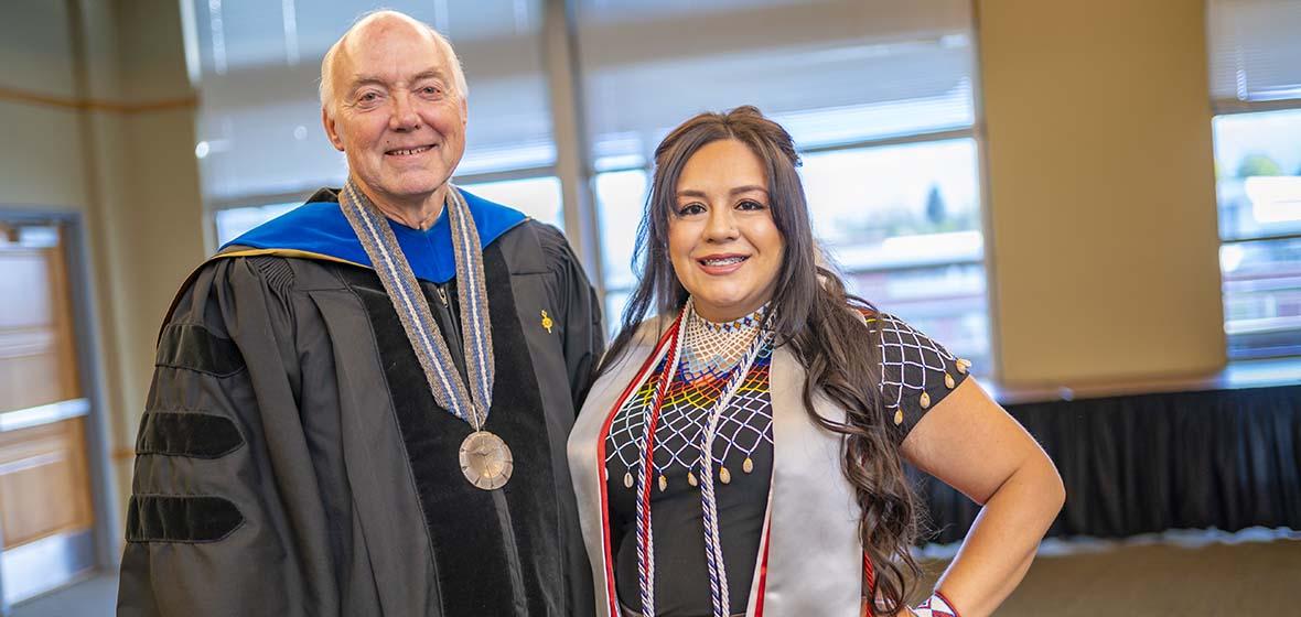 Marc Johnson wearing a graduation robe and Christina Thomas wearing traditional Paiute regalia