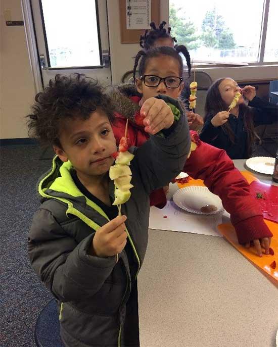 children making fruit kabobs