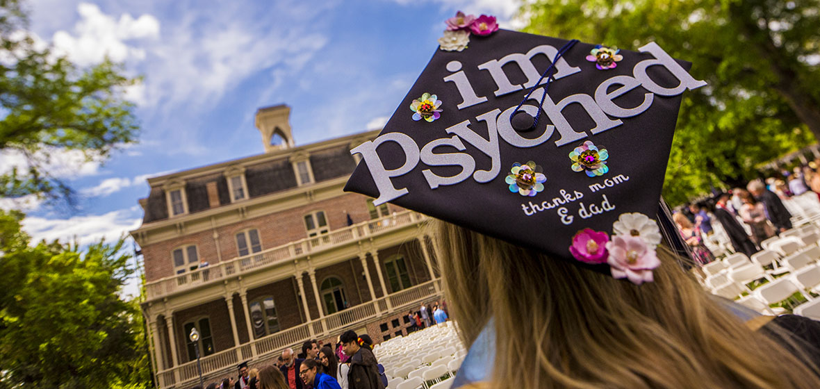 "Graduate facing Morril Hall with a mortar board that reads, ""I'm psyched. Thanks Mom & Dad"""