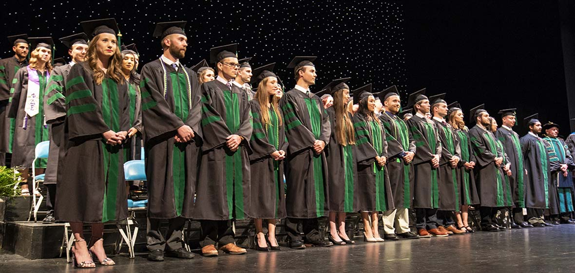 Graduates in black robes and green stoles standing on a stage