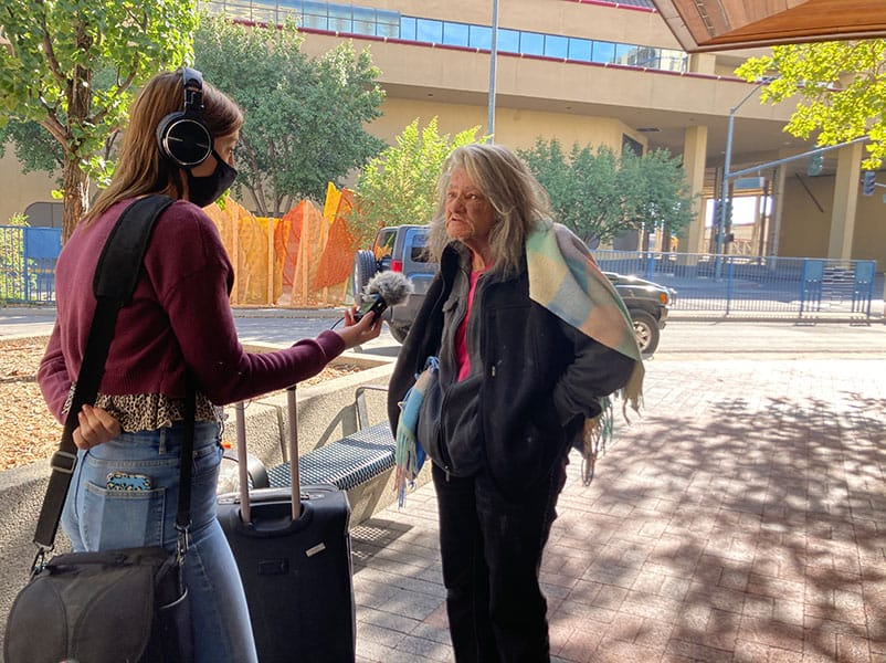 """Un estudiante entrevista a una mujer que está sin hogar. """"Class ="""" img """"/> <figcaption class="""