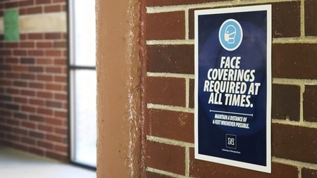 A poster indicating that face coverings are required at all times on the wall of a parking garage